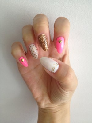 Natural stiletto nails with gold polish and glitter detailing