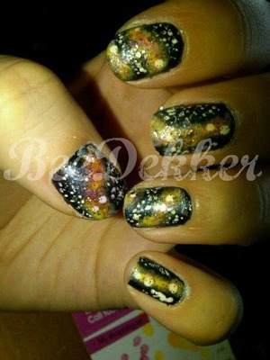 This amazing! design was so much fun to create. Simply paint your nails black and let dry. Then using a makeup sponge, sponge white, yellow and light pink in a smooth line down each nail in any direction you like. Using a dotting tool apply little white dots as stars. Finish off with a layer of glitter to give the look of even more stars. enjoy!