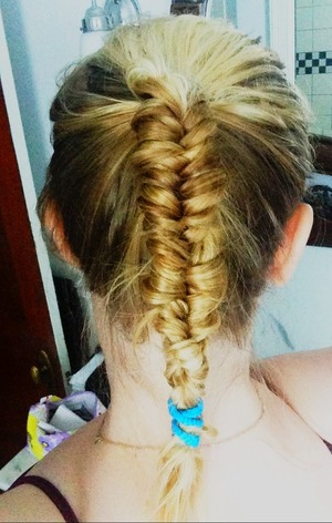 I don't know why people are so frightened of doing fishtails. They're easier to do than a regular braid, in my opinion! Here, I started with a high ponytail. Notice, I'm not afraid of colored hair bands. :)