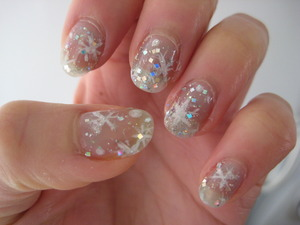 icy snowflake nails: pale blue flakes/glitter underneath, then snowflakes topped with microglitter, lastly a top coat with small and large glitters