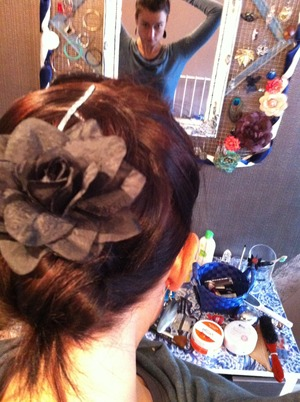 pin front hair back, mimicking a half-ponytail. Twist hair into low bun, fasten. Add flower pin. Done.