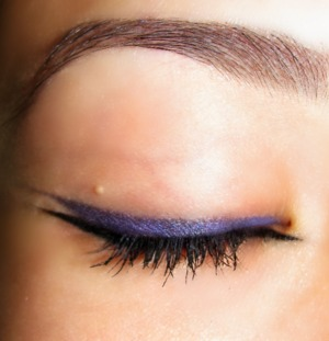 The purple was achieved by layering purple eyeshadow over a black smudge stick eyeliner with a wet cotton swab.