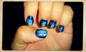 Used a dark blue polish first, then with a piece of a make up applicator sponge I added white to the middle and a lighter blue around the edges of the white. Topped it with China Glaze Luxe and Lush flakes polish and a top coat. Looks so pretty in direct light.