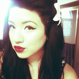 Winged eyeliner and red lips.