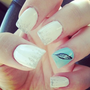 White nails with a silver gradient glittler and a teal accent nail with feather.