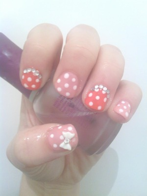 Pink polka dot nails with rhinestones and a bow