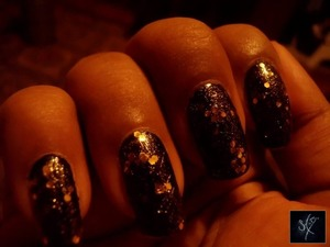 Black nail polish with chunky gold glitter polish from Charlotte Russe.