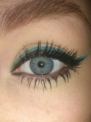 Green and blue lined thickly then black gel eyeliner thinner on top. Twist on a classic cat eye