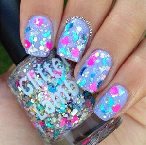 """This glitter topper is called """"Plastic Doll House"""" and is worn by @allaboutnails247 . Plastic Doll House Glitter Nail Polish is a clear base filled with blue holographic moons, silver holographic triangles, neon pink hearts, gold and silver hex and square mix and rainbow holographic hex tiny glitters."""
