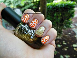 White nails, added orange leopard print with a nail art pen, then painted my ring fingers gold with LA Girl Glitter Addict in Synergy.