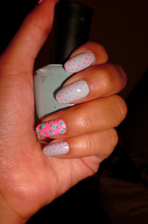 Blue background with neon dots, and accent thumb and ring finger with neon pink background and blue flowers.