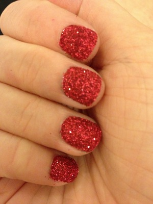 I started with OPI Nail Envy as my base, then one coat of Avons Real Red polish (no point in using an expensive brand for this). Once that was dry I did one nail at a time, painting on one coat of Sally Hansens Hard as Nails, and dipping straight in to a pot of fine red craft glitter, once i had done 10 nails and brushing off excess glitter, I put on a thick coat of Seche Vite Dry Fast Top Coat, just to smooth out the surface to stop the glitter catching on my clothes. These nails dry rock solid and last 3 - 4 days depending on level of activity with your hands.