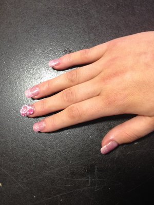 French tipped acrylics covered with glittery pink gel polish then on one finger covered in gems and heart nail art pieces
