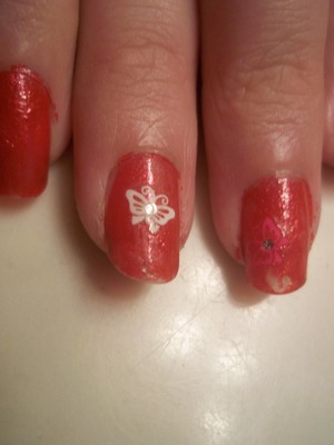 Orange polish with flower and butterfly stickers
