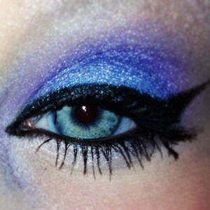 Blue eyeshadow with purple in the crease. White underneath the eye. Black glitter cateye.