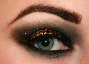 A simple smoky black eye with red accent and a dramatic gold winged liner 