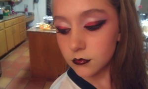 """My little cousin wanted me to do her makeup. I said, """"What color?""""  """"Red and black!"""" """"Dramatic or normal?"""" """"Dramatic!""""  So yeah. She has hard to work with eyelids, so I had to cut her crease in a way I'm not used to. Aaaand, that's it! I used shadows from a huge e.l.f. pallet, and Nyx's Jumbo Eyeshadow Pencil in Milk. For the lips, I mixed eyeshadow (sounds icky, but it works and I'm a teen on a budget), and clear lipgloss (vanilla mint flavored, from Bath and Body Works). And then drugstore foundation/pressed powder. She's such a sweetie.  The crease isn't exactly straight but I was rushed."""