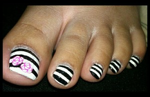 white toe nails with black stripes and a rose fimo accent!! :)