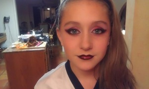 """My little cousin wanted me to do her makeup. I said, """"What color?""""  """"Red and black!"""" """"Dramatic or normal?"""" """"Dramatic!""""  So yeah. She has hard to work with eyelids, so I had to cut her crease in a way I'm not used to. Aaaand, that's it! I used shadows from a huge e.l.f. pallet, and Nyx's Jumbo Eyeshadow Pencil in Milk. For the lips, I mixed eyeshadow (sounds icky, but it works and I'm a teen on a budget), and clear lipgloss (vanilla mint flavored, from Bath and Body Works). And then drugstore foundation/pressed powder. She's such a sweetie."""