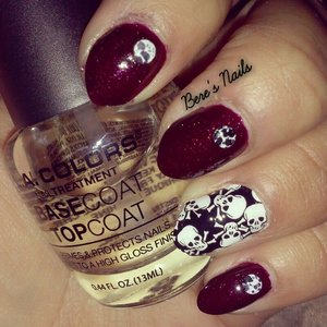 Burgundy red glitter base nails accented with round black and white splattered studs. Accented the ring finger with a skull design nail wrap.