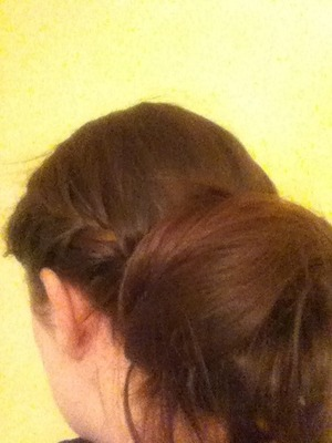 Part the hair to one side. French braid, staying close to the hair line. Finish the look with a loose bun.