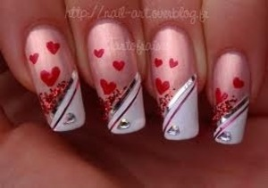 Light pink nail polish white and black and a pink stick on heart