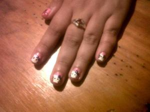 Hello Kitty on each nail with pink background and purple bow.