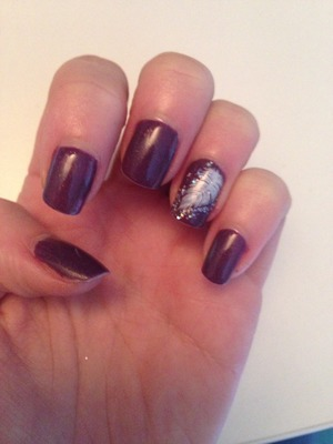 Deep purple shellac with a white feather surrounded by a dusting of silver Nails zinc glitter