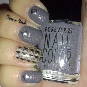 A swatch of a gorgeous cement gray jelly polish with very fine silver glitter. Used a nail wrap for an accent nail that creates the illusion of a studded nail. Accented the rest of the nails with actual silver square studs.