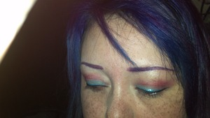 Sorry about the bad lighting. This eye look went well with my purple hair at the time. Soft pink in the crease, which faded into a bright blue. Black eyeliner was used, with a strip of blue glitter liner just above that. I used Physician's Formula gel liner from the Hazel collection to color my brow a nice purple.