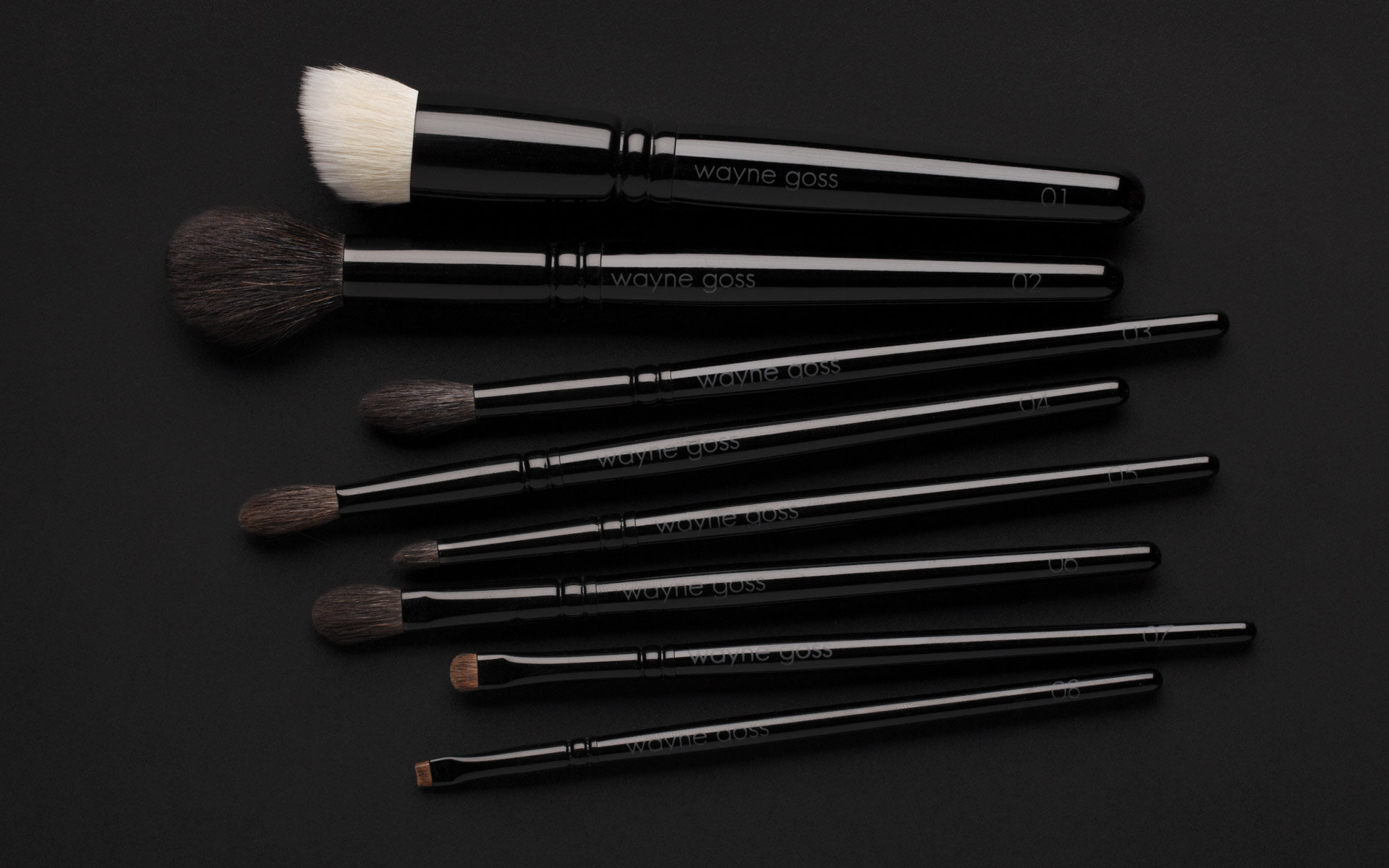 The Wayne Goss Collection, all 8 brushes in the colleciton lying flat showing scale and labels.