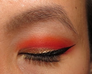 A gold and bright orange look with winged liner
