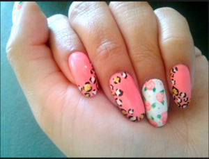 Accent nails in white with floral flowers. Rest of the nails in coral with cheetah print
