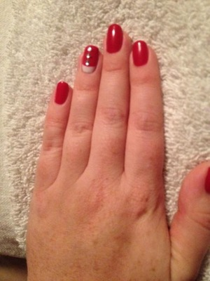 Red nails with a white reverse french tip accent nail