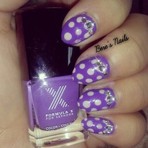 Purple base nails polka-dotted in a lighter lavender purple polish. Accented all the nails with two different sized clear rhinestones.