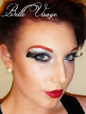 black and silver smoky eye with feather lashes red glitter eyebrows and a blood red lip