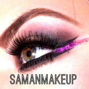 A fierce smokey eye with a pop of purple glitter in between the double-winged liner!