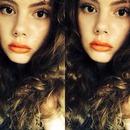 Rockin' some orange lipstick.