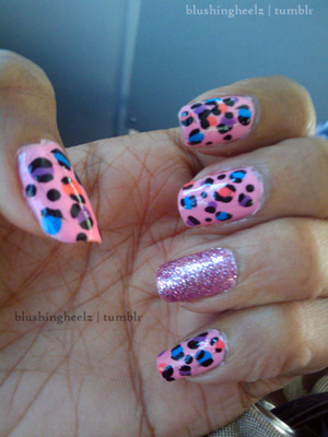 Pink nails with leopard print (blue, coral and purple) with one accent nail that's full of glitter.