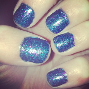 Blue nail polish with blue and purple glitter.