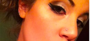 Bronzed and Luminized face with a smoked and winged out eyeshadow look.