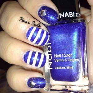 navy blue base topped with a fine glitter and accented them with silver square studs. for the rest of the nails i added some white stripes!