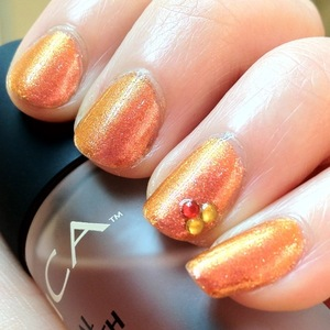 """This manicure gives me such a fall/halloween feeling. It's like fire and pumpkin on your fingertips! Glitter Gal Fiery Furnace Brilliant Shade shifter is totally gorgeous and really reminds me of looking into the depths of a fire; the Deep purple song """"Into the fire"""" came to mind, hence the title. It glows orange, yellow, light red, rose gold, and a little brown at different angles and under different lighting. Amazing!  I used Revlon Clear Nail Enamel (771) to attach the rhinestones and a top coat later over that to keep them locked in."""