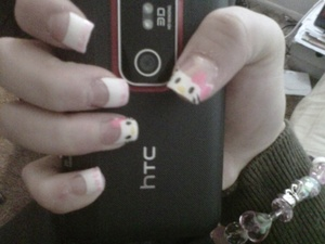 hello kitty french tips with pink sparkles on free edge of other nails.