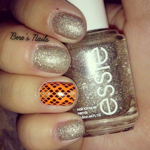 A simple gold/silver base. Accented a nail with an orange tribal nail wrap.