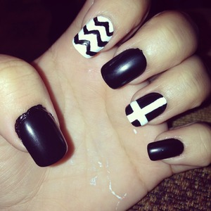 Black nails with a white cross and a black and white chevron design.