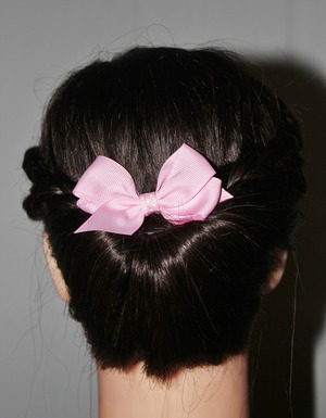A casual updo with braided sides, and pink bow.