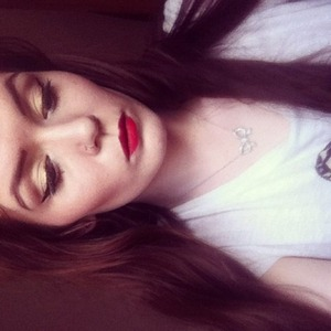 Red lips, contoured cheeks, gold and black liquid eyeliner, dramatic brows.