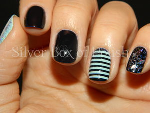 Mint and navy manicure using striping tape and glitter.