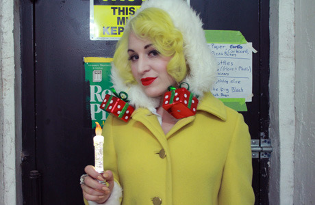 Mischa is looking pin-up perfect in Lime Crime Velveteen lipstick, warm yellow curls, and garishly giftable earrings.